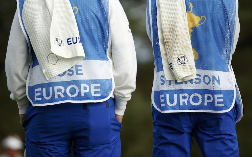 The caddies of European Ryder Cup players Justin Rose and Henrik Stenson wait on the green during their fourballs 40th Ryder Cup match at Gleneagles